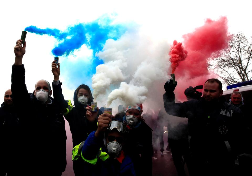 French ambulance drivers hold blue, white, red smoke bombs during a demonstration at the Place de la Concorde in Paris, France, December 3, 2018.