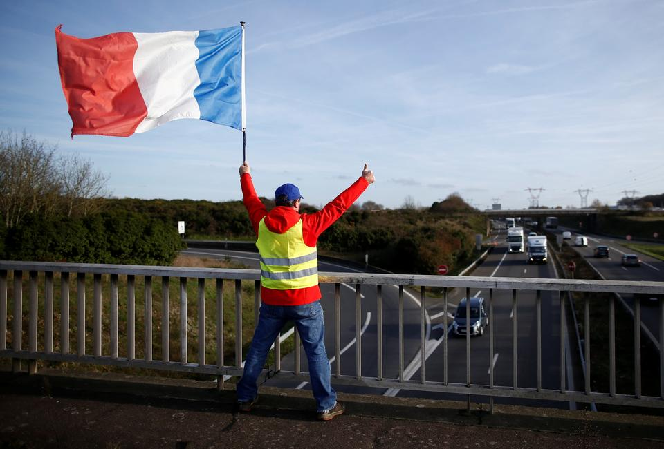 A man wearing a yellow vest and holding a French flag stands on a bridge near the Nantes Atlantique Airport as the