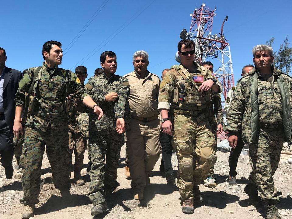 A US military commander (2nd R) walks with YPG militants at the group's headquarters, which were hit by Turkish air strikes in Mount Karachok, near Malikiya, in northern Syria on April 25, 2017.