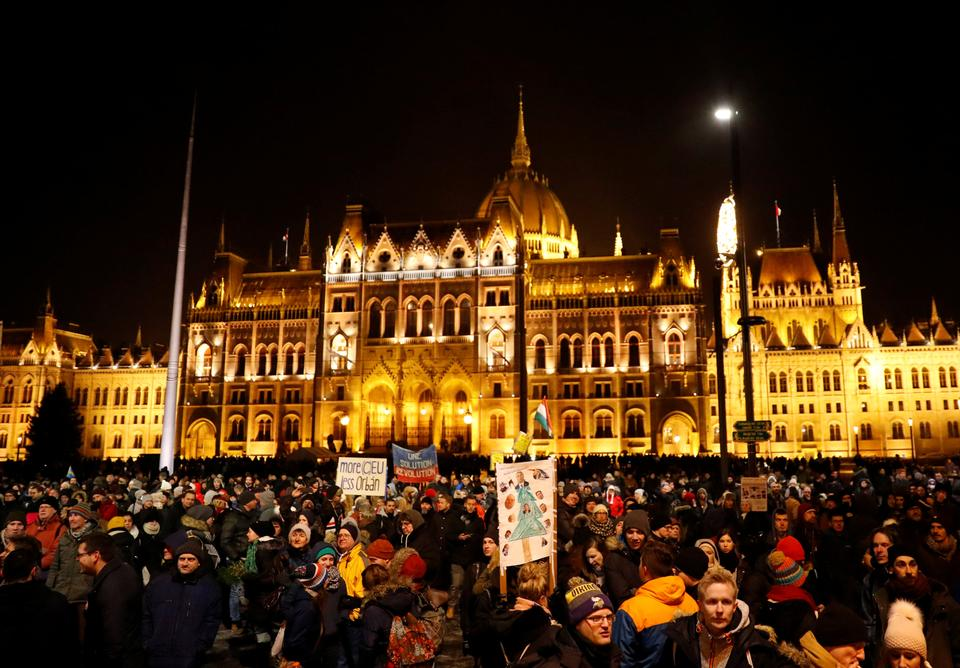 People stand in front of the parliament building during a protest against a proposed new labor law, billed as the