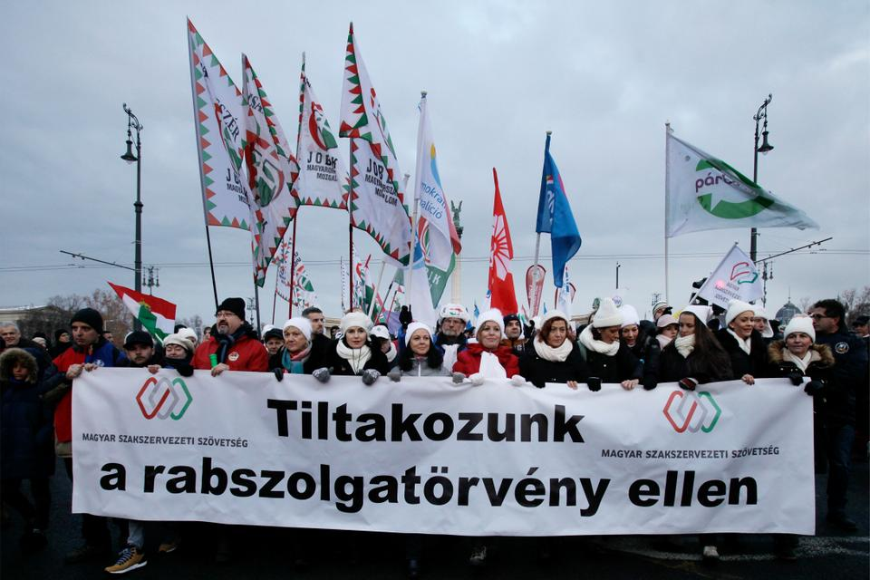 Members and sympathisers of several trade unions, political parties and civil organisations march with a banner reading 'Protest against slave low', in Budapest on December 16, 2018 to protest against changes to the labour code proposed by the Prime Minister's party.