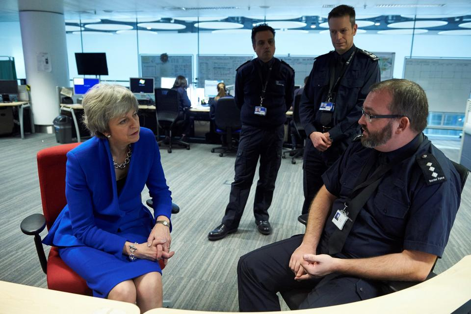 Britain's Prime Minister Theresa May (L) talks with UK Border Force officers as she visits their Command Centre during her visit to Terminal 5 at London Heathrow Airport in west London on December 19, 2018.