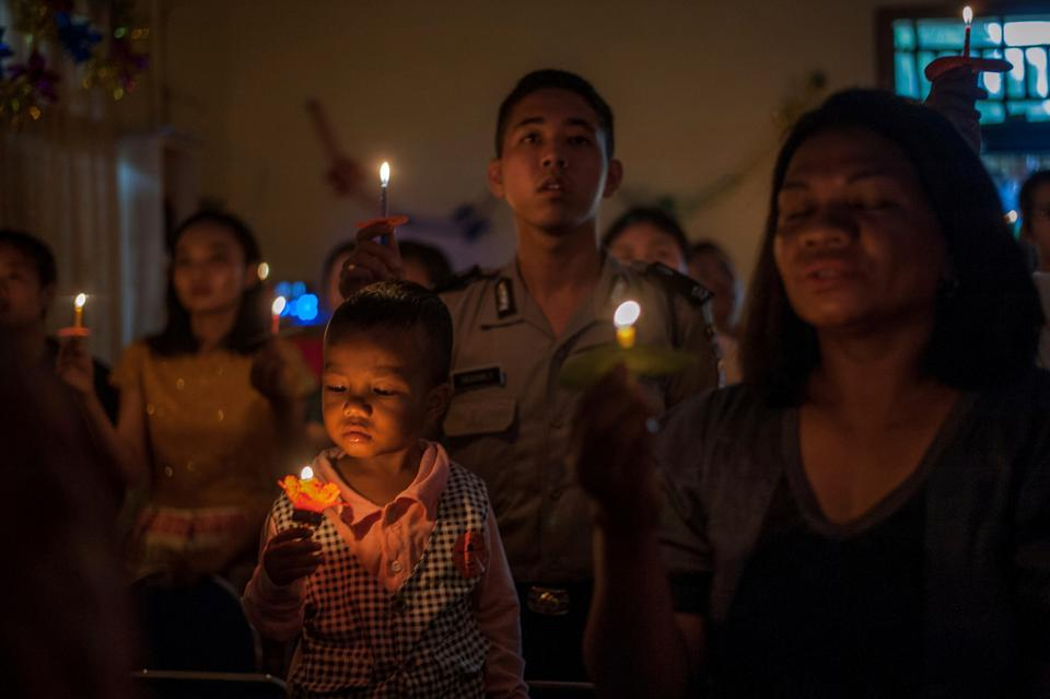 People attend a Christmas service at Rahmat Pentecostal Church in Carita, Indonesia. The celebrations were replaced by somber prayers for tsunami victims in an area.