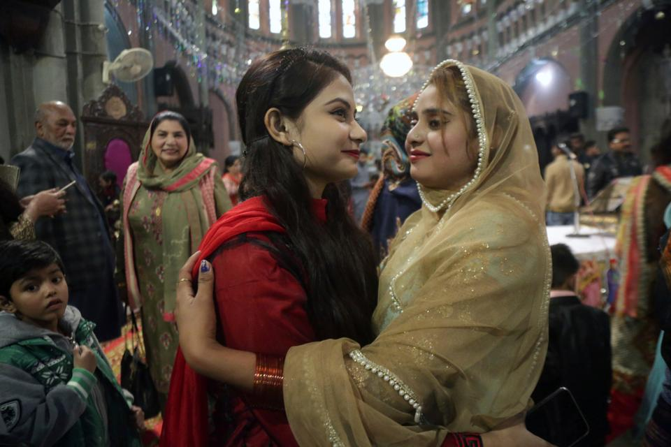 Christian girls greet each other after attending a Christmas Mass at a church in Lahore, Pakistan.