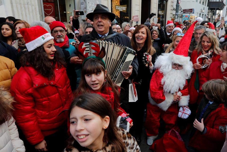 Zografyon Greek School principal Yani Demircioglu, surrounded by Greek Orthodox children, plays an accordion during a Christmas celebration at the main shopping and pedestrian street of Istiklal in central Istanbul, Turkey.