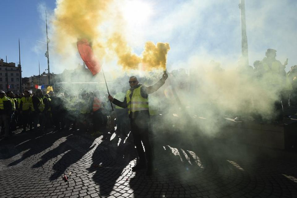 A Yellow Vest (Gilets jaunes) protester lights a flare during an anti-government demonstration called by the Yellow Vest movement in Marseille, southern France, on January 12, 2019.
