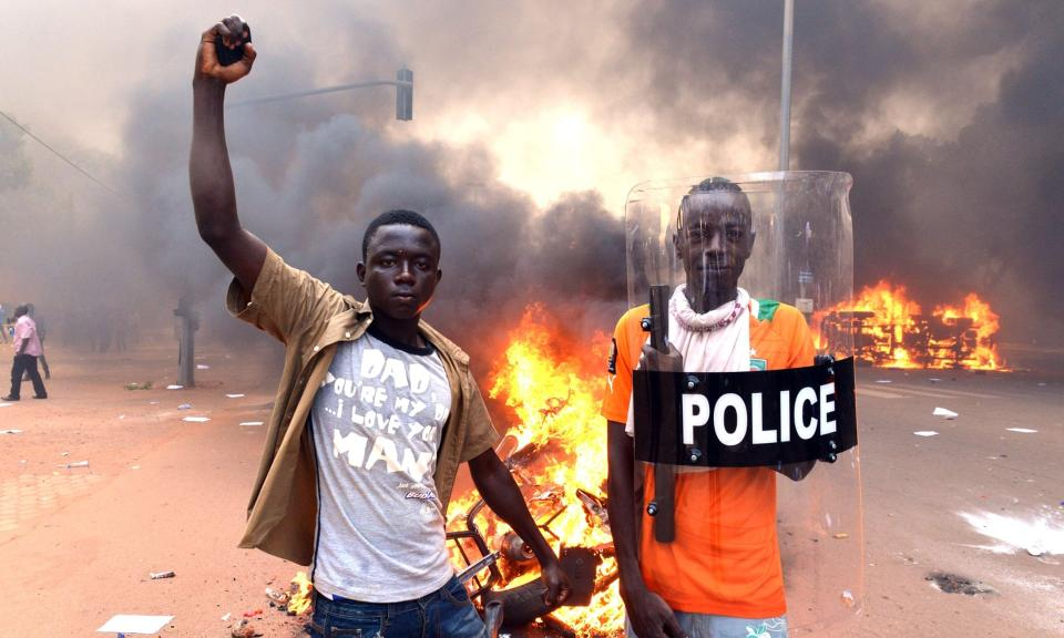 Protesters pose with a police shield outside the parliament in Ouagadougou on October 30, 2014.