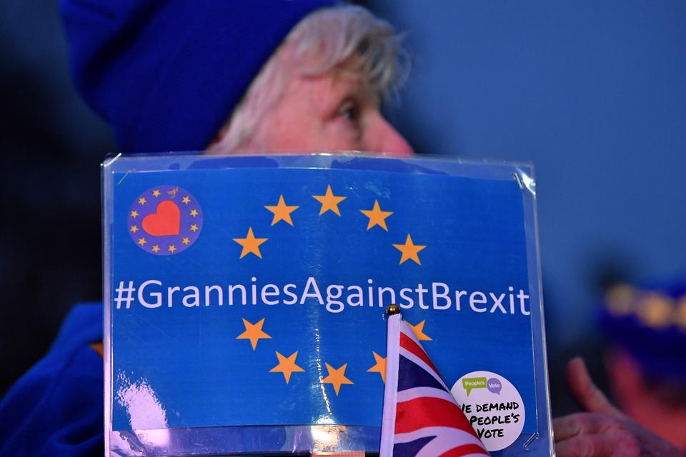 An Anti-Brexit activist holds a placard reading