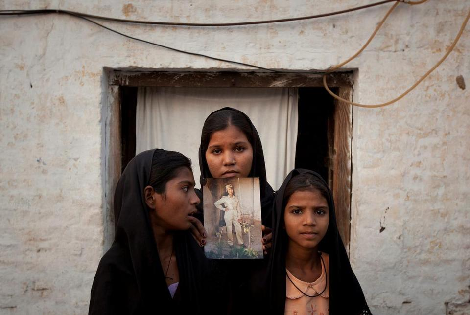 The daughters of Pakistani Christian woman Asia Bibi pose with an image of their mother while standing outside their residence in Sheikhupura located in Pakistan's Punjab Province, November 13, 2010.