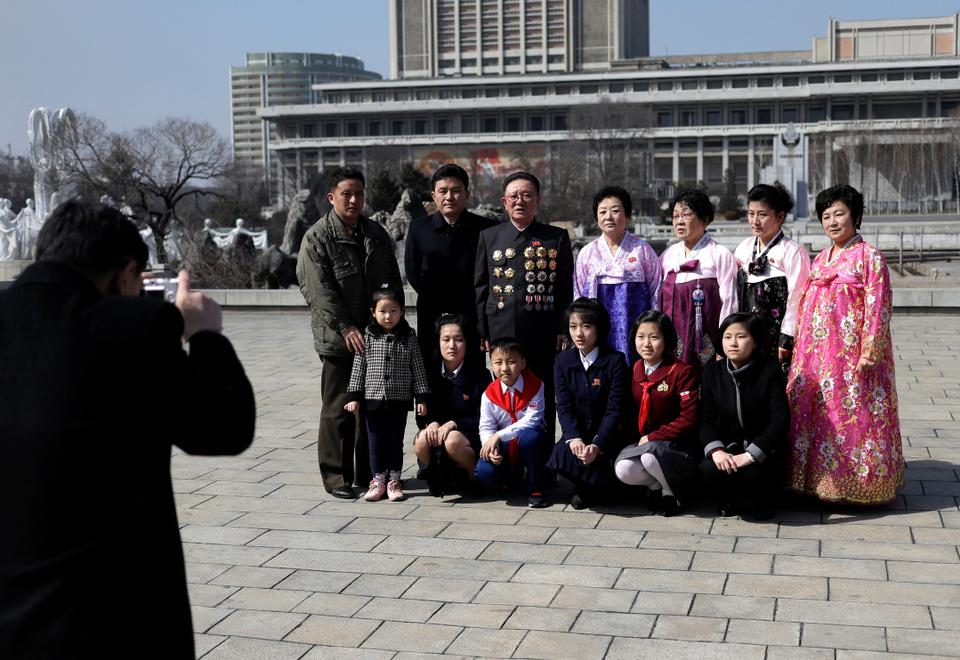 A North Korean family has their photo taken as they mark the International Women's Day in Pyongyang, North Korea, Friday, March 8, 2019.