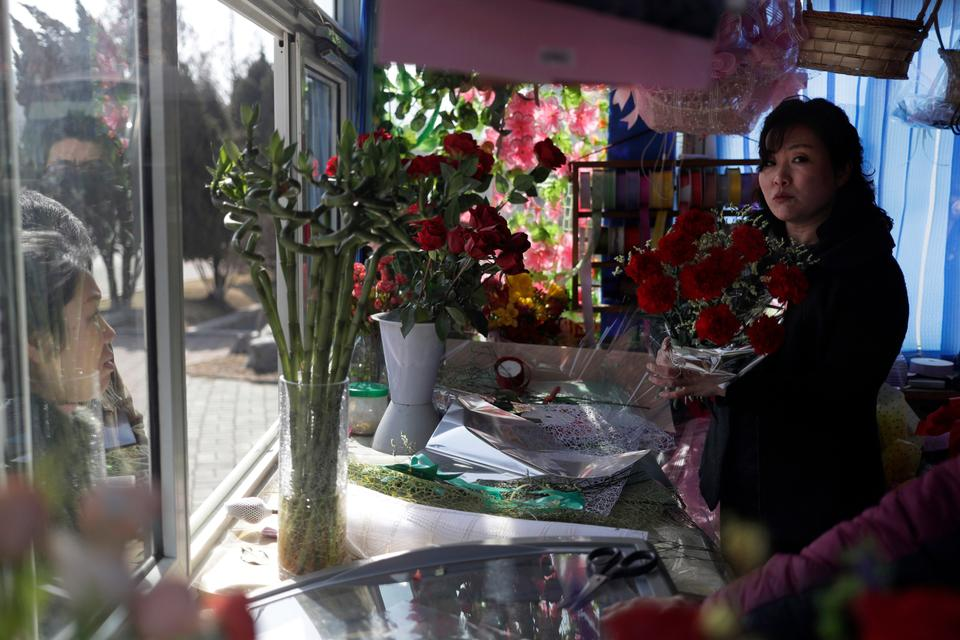 A vendor prepares a flower bouquet for customers as people mark the International Women's Day in Pyongyang, North Korea, Friday, March 8, 2019.