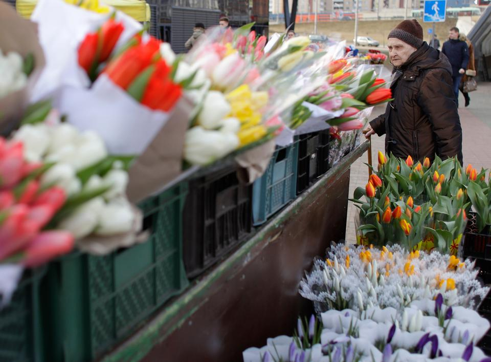 An elderly woman passes by flowers at a street market on the eve of the International Women's Day in Minsk, Belarus, Thursday, March 7, 2019.