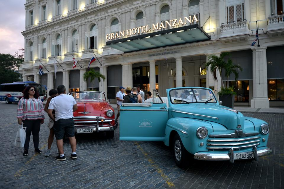 Tourists stand next to an old American car in front of the Gran Manzana Hotel in Havana, on February 11, 2019.