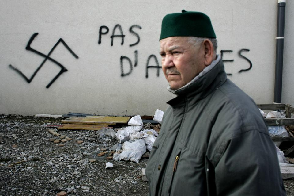 A Muslim resident walks past racial slurs painted on the walls of a mosque in the town of Saint-Etienne, central France, Monday Feb.8, 2010. The French Council of the Muslim Faith says such vandalism has multiplied in France