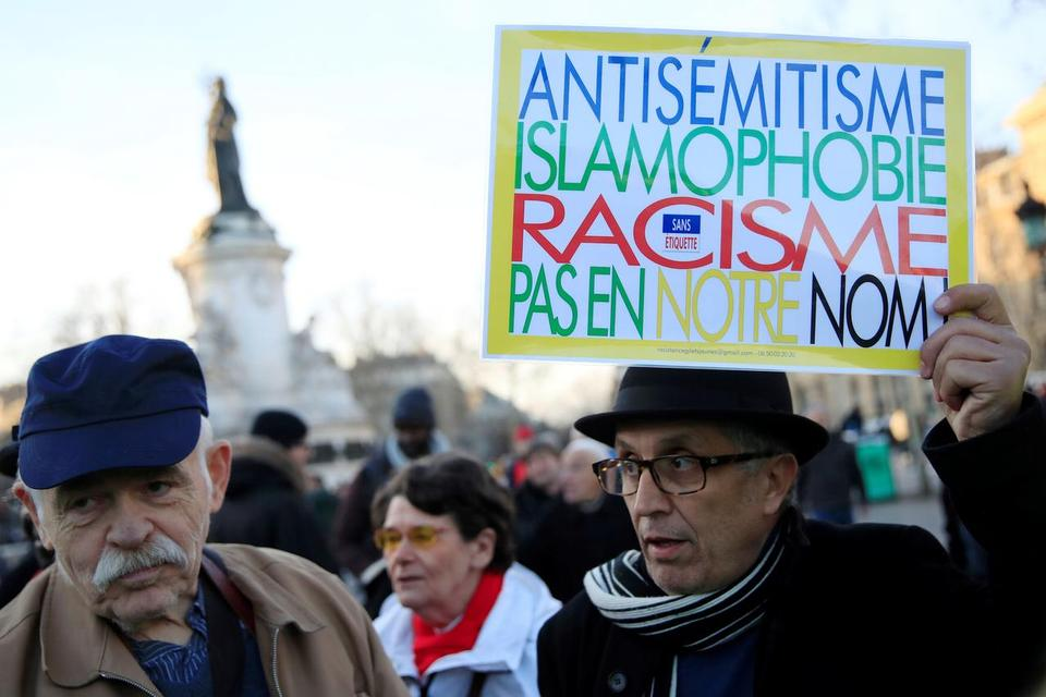 People attend a national gathering to protest antisemitism and the rise of anti-Semitic attacks in the Place de la Republique in Paris, France, February 19, 2019. The writing on the sign reads: