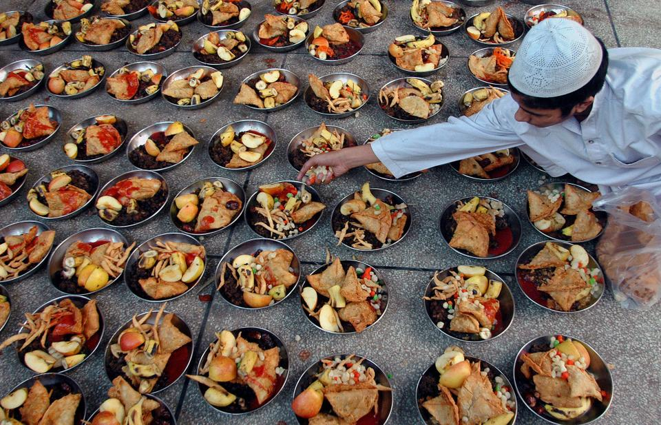 A Pakistani Muslim boy arranges dishes of fruits and other stuff for Iftar [File:K M Chaudhry/AP Photo]