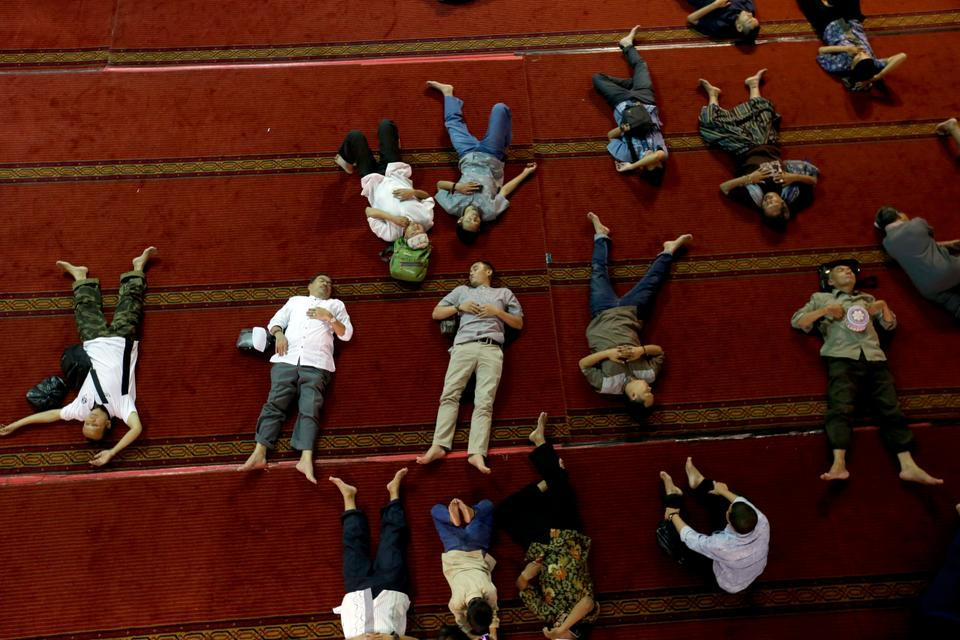 Indonesian men take siestas in order to whittle down the hours before iftar. [File:Tatan Syuflana/AP Photo]