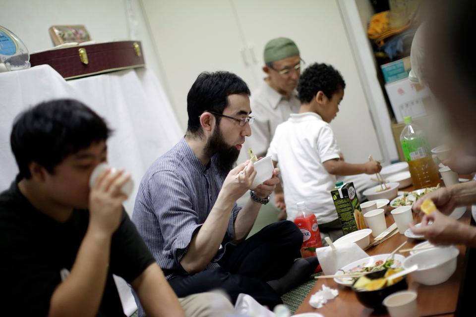 Japanese Muslim, Yohei Matsuyama (centre) breaks his fast with other Muslims in Tokyo [Eugene Hoshiko/AP Photo]