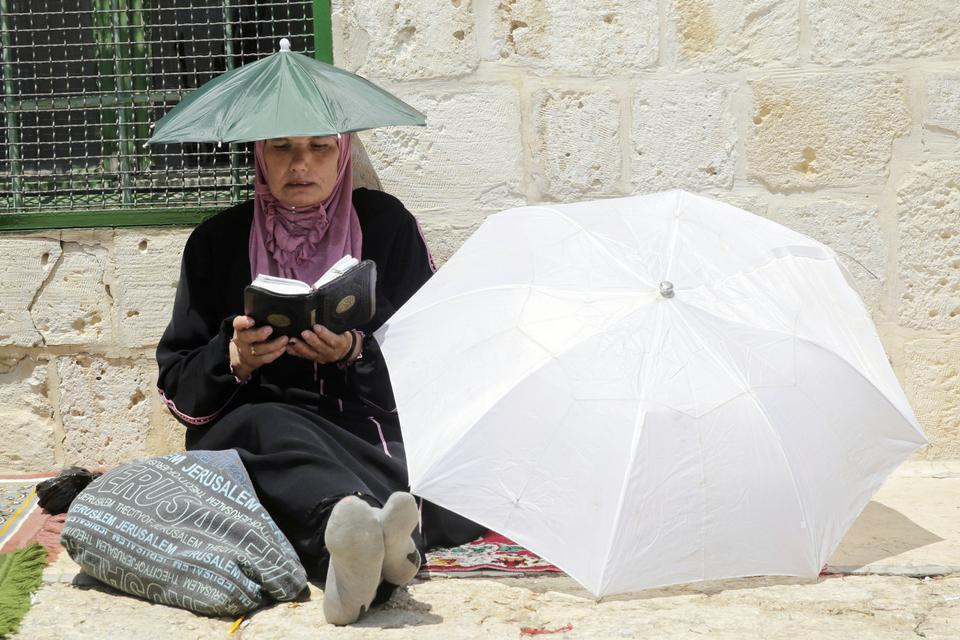 A Palestinian woman reads the Quran outside the Al Aqsa Mosque during Ramadan fasting [Mahmoud Illean/AP Photo]
