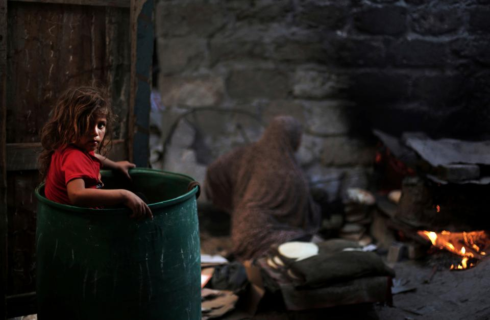 A Palestinian girl plays in a barrel as her mother bakes bread for a Ramadan dinner at their house in el-Zohor slum in Gaza [Khalil Hamra/AP Photo]