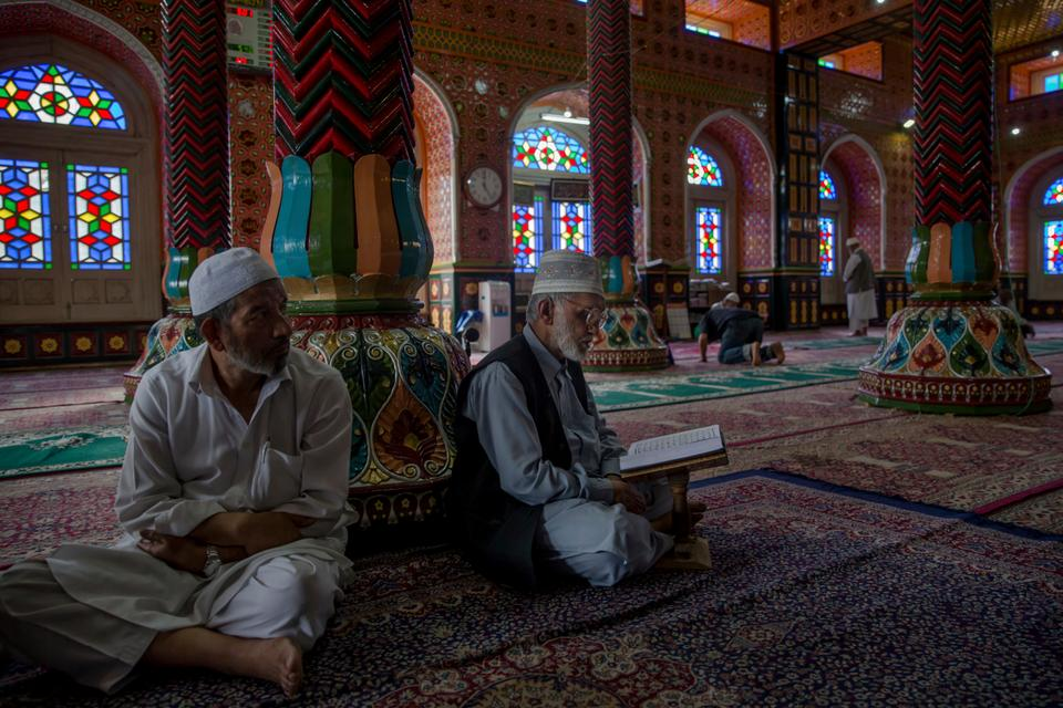 Elderly Kashmiri men read verses from the Quran at a mosque in Srinagar [Dar Yasin/AP Photo]