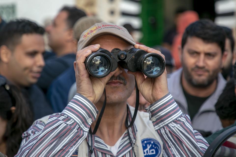A man peers through a pair of binoculars in order to spot the new moon. [Yassine Gaidi/Anadolu Agency]