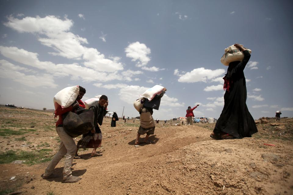 Yemenis carry food aid distributed by a charity ahead of Ramadan [Khaled Abdullah/Reuters]