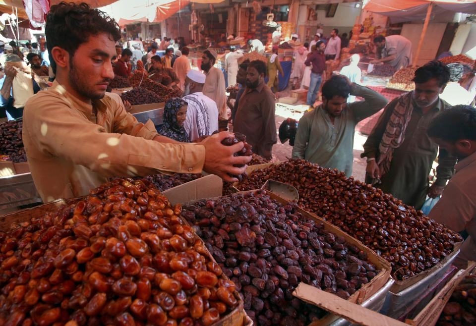 A vendor weighs up dates in the Pakistani commercial hub of Karachi [Fareed Khan/AP Photo]
