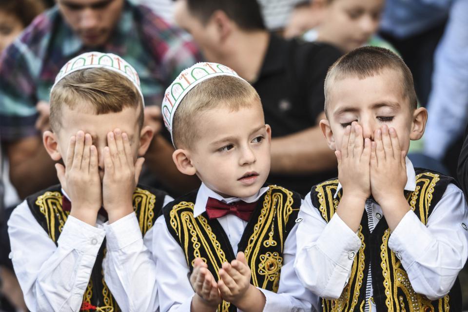 Three young Albanian boys celebrating Eid