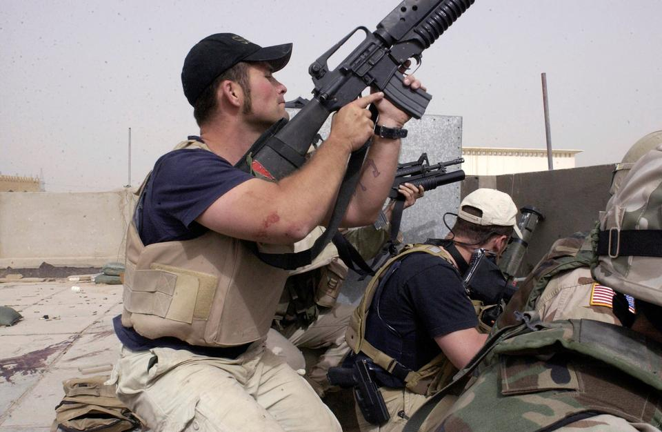 In this April 4, 2004 file photo, plainclothes contractors working for Erik Prince's Blackwater USA take part in a firefight in Iraq.