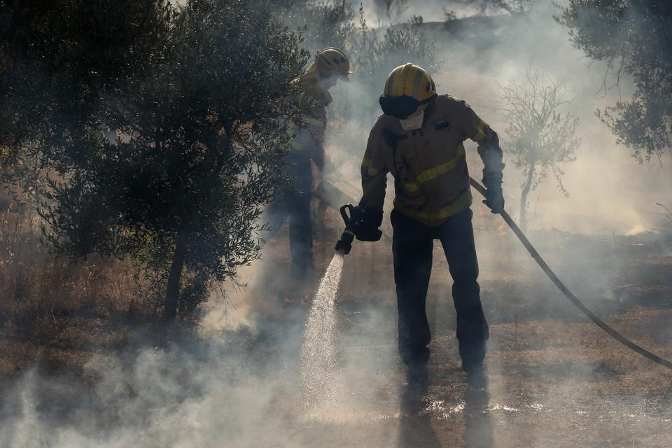 Firefighters try to control a forest fire raging near La Torre de  l'Espanyol in the northeastern region of Catalonia on June 27, 2019.