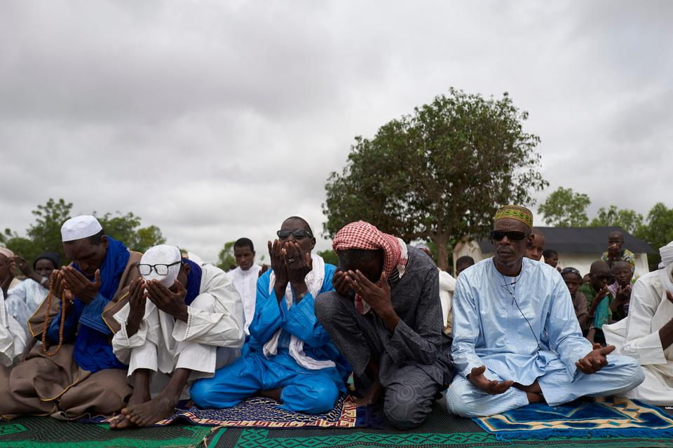 Fulani displaced men pray during the Eid al Adha (Feast of Sacrifice) in a refugee camp in Bamako on August 11, 2019.