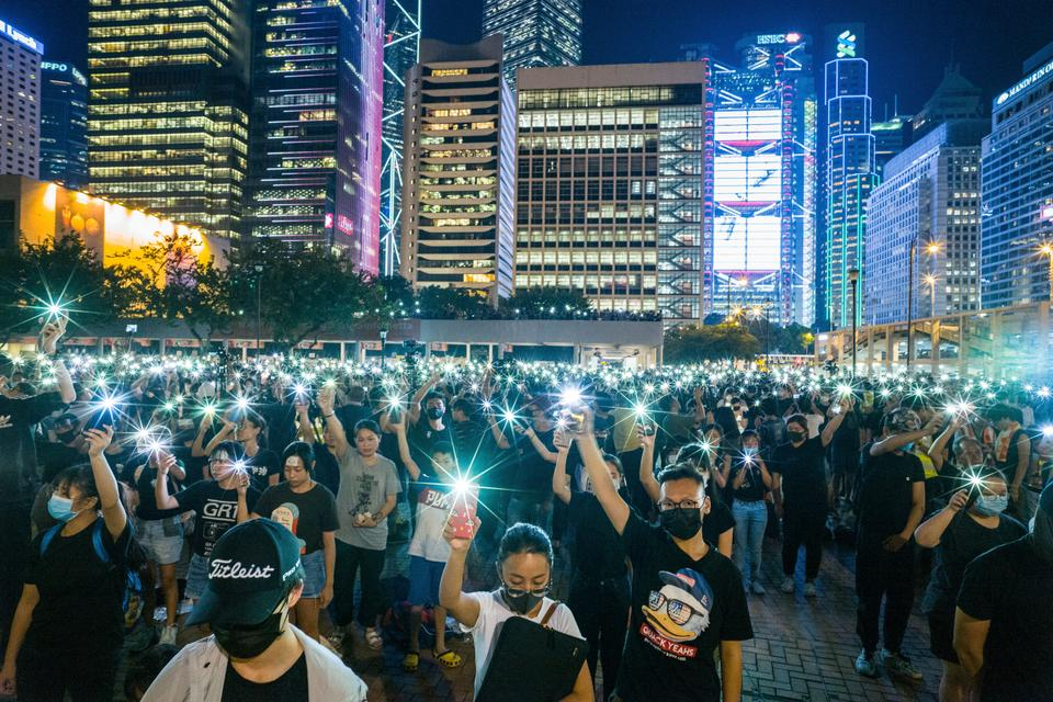 Secondary school students raise their phone torches as they sing 'Do You Hear the People Sing' from 'Les Miserables' while attending a rally at Edinburgh Place in Hong Kong on August 22, 2019.