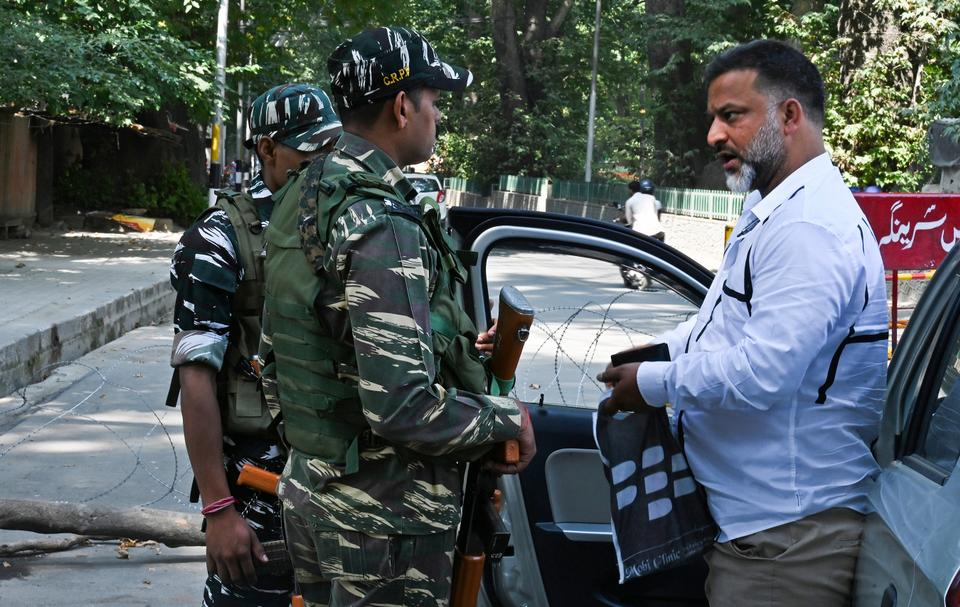 Indian paramilitary soldiers question a motorist at a roadblock during a lockdown in Srinagar on September 3, 2019.