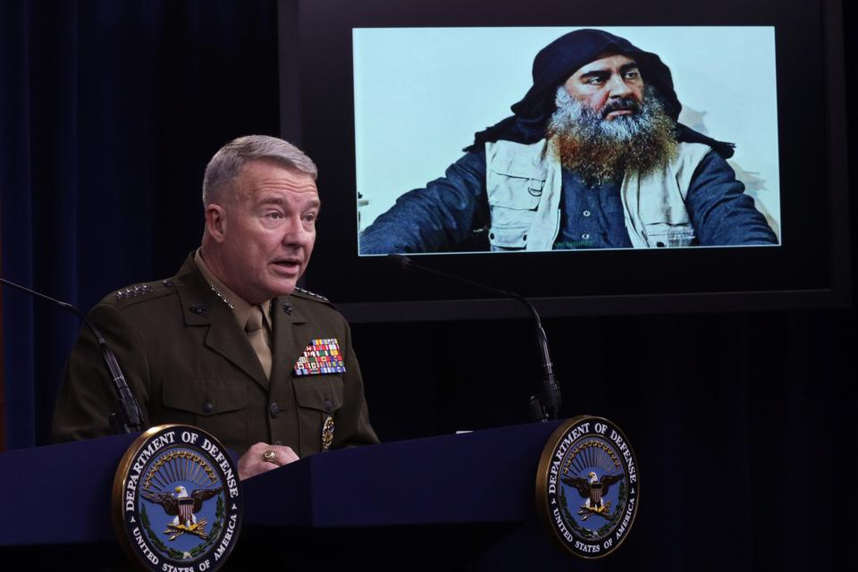 US Marine Corps Gen. Kenneth McKenzie, commander of US Central Command, speaks as a picture of Abu Bakr al-Baghdadi is seen during a press briefing October 30, 2019 at the Pentagon in Arlington, Virginia. Gen. McKenzie and Hoffman spoke to the media to provide an update on the special operations raid that targeted former ISIS leader Abu Bakr al-Baghdadi in Idlib Province, Syria
