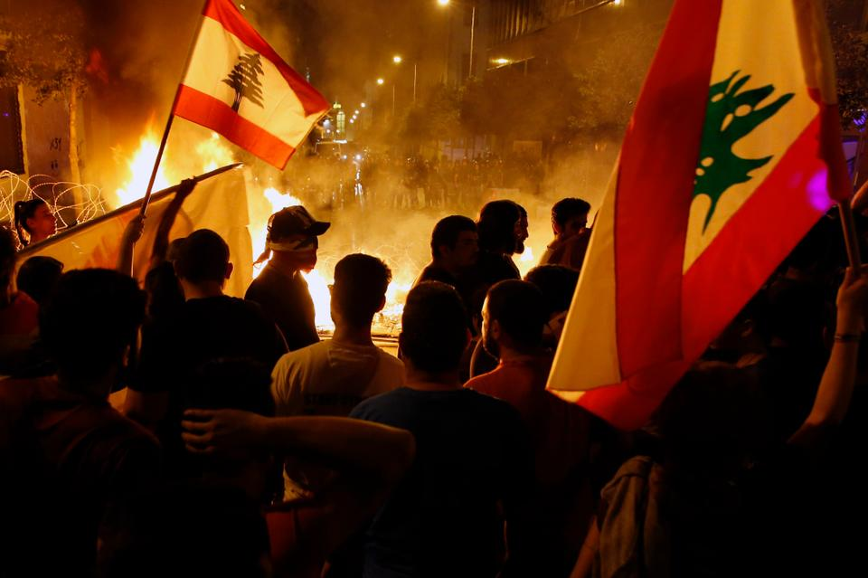 Anti-government protesters wave Lebanese flags in front of a barricade on fire on a road leading to the parliament building, during ongoing protests against the government, in Beirut, Lebanon, Wednesday, Nov.ember 13, 2019.