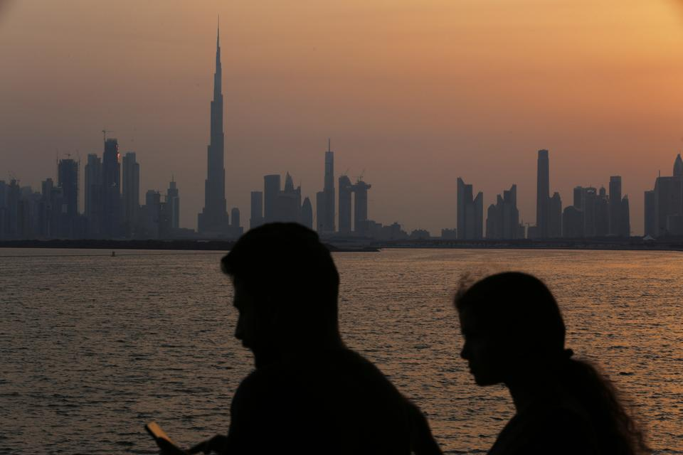 A couple look at a picture on a mobile phone as the sun sets over the Burj Khalifa, the world's tallest building, in Dubai, United Arab Emirates, Friday, May 18, 2018.