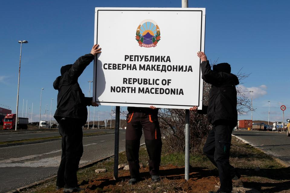 Workers install a new road sign with the name Republic of North Macedonia in the southern border with Greece, near Gevgelija, Wednesday, Feb. 13, 2019.