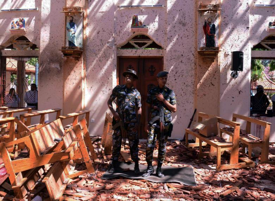 Sri Lankan military stand guard inside a church after an explosion in Negombo, April 21, 2019.