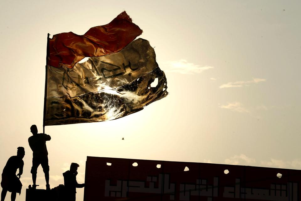 An Iraqi demonstrator carries an Iraqi flag during ongoing anti-government protests, in Baghdad, Iraq, December 10, 2019.