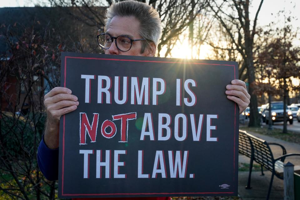 A protester holds a sign in support of the impeachment of U.S. President Donald Trump during a rally near the home of U.S. Senator Mitch McConnell in Louisville, Kentucky, December 23, 2019.