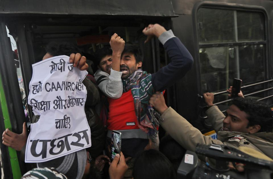 Policemen push students into a bus after they are detained during a protest outside Uttar Pradesh Bhawan in New Delhi on Dec. 27, 2019. They were protesting against the growing police brutality in Uttar Pradesh state.