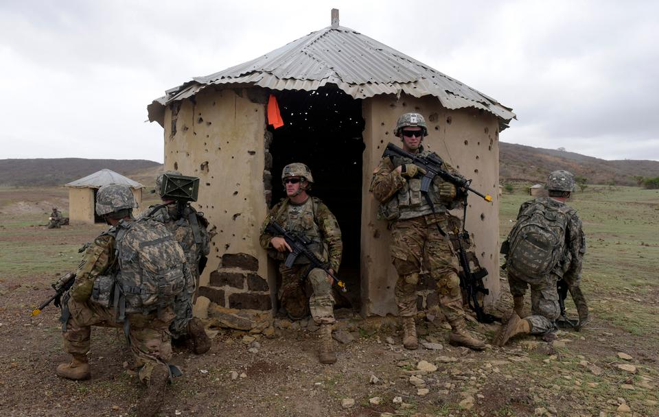 In this file photo taken on July 25, 2016 American soldiers of 1st Battalion, 30th Infantry Regiment, 2nd Infantry Brigade Combat Team, 3rd Infantry Division take position near a hut during a combined training exercise with Senegalese 1st Paratrooper Battalion in Thies.