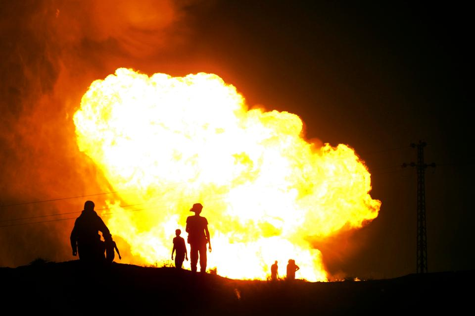 Egyptians watch as smoke and flames rise after masked gunmen blew up a terminal of the Egyptian natural gas pipeline to Israel in July, 2011.