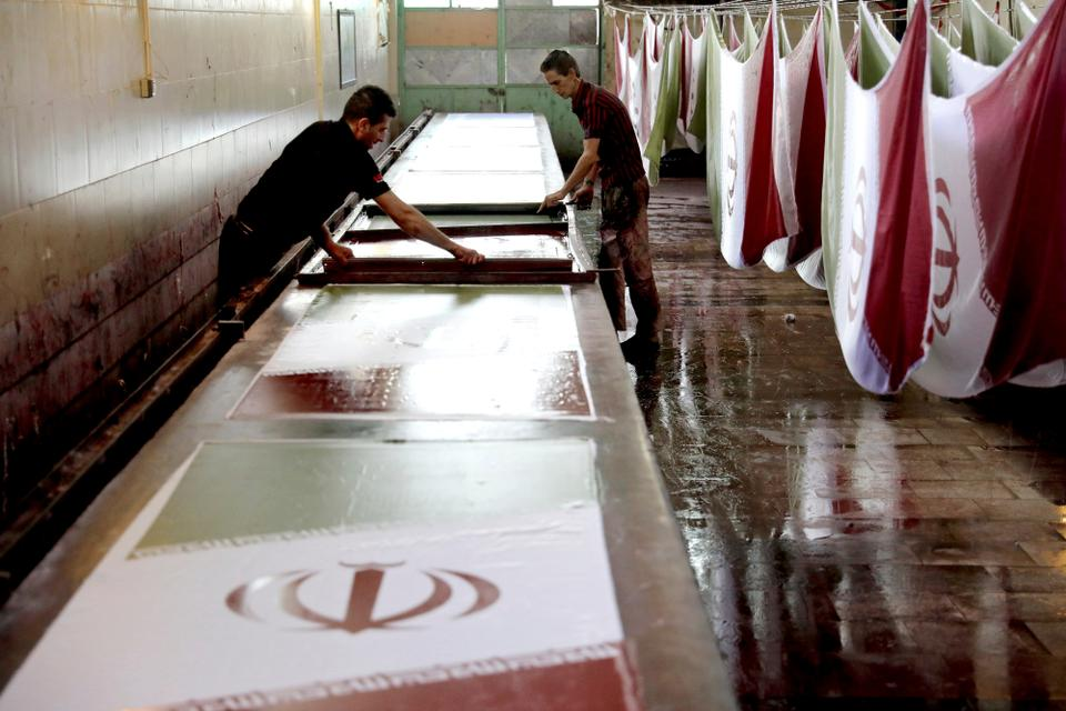 In this February 8, 2020 photo, workers use a silk screen to print Iranian flags at the Diba Parcham Khomein factory in Heshmatieh village, a suburb of Khomein city in central Iran.