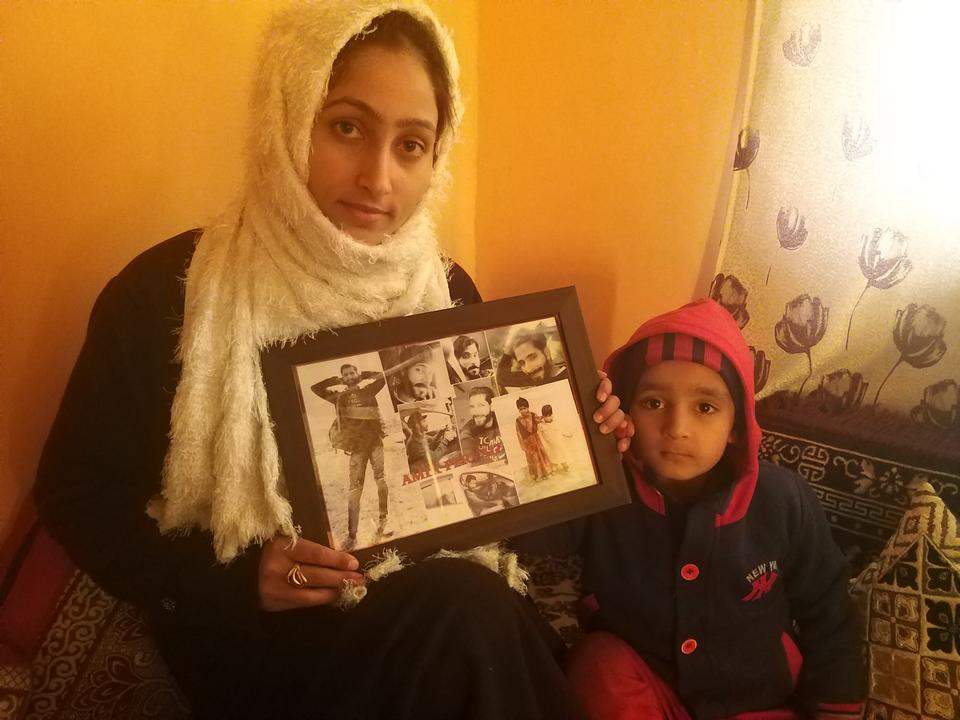 Maryam Rasool and her three-year-old son, Atif Amir, holding a collage of photos of Amir at their residence in north Kashmir.