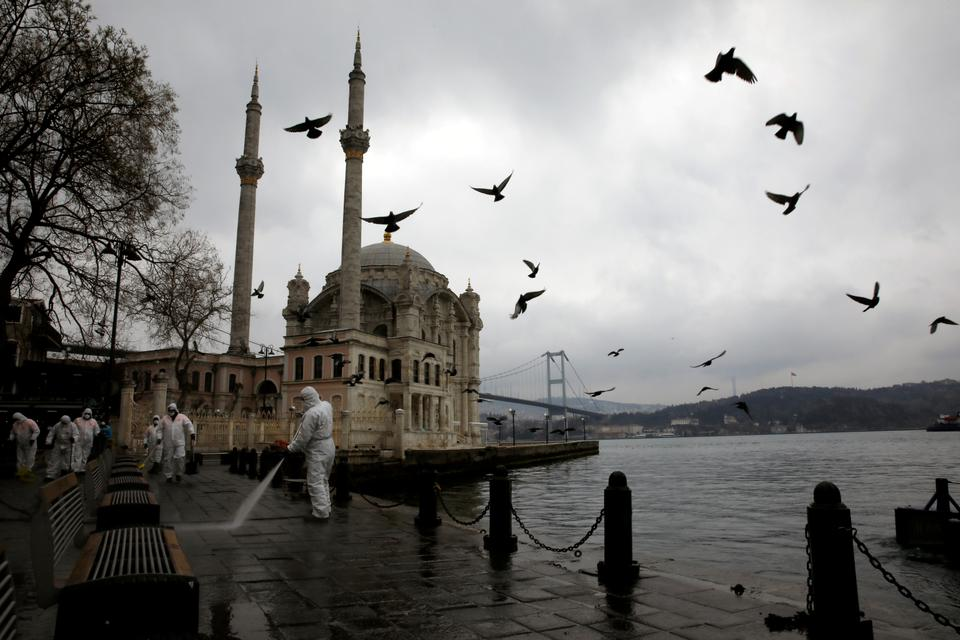 A worker sprays disinfectant outside Ortakoy Mosque, to prevent the spread of coronavirus disease (COVID-19), in Istanbul, Turkey, March 23, 2020.