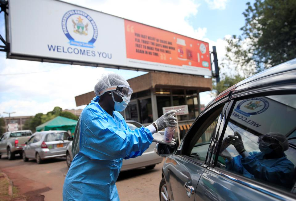 A health worker screens and sanitises visitors to prevent the spread of coronavirus disease outside a hospital in Harare, Zimbabwe March 26, 2020.