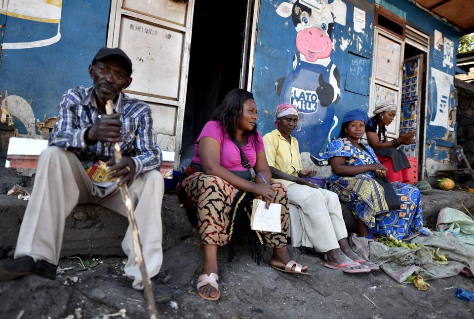 Traders sit near a deserted crossing point between the Democratic Republic of Congo and Rwanda at the Petite Barriere in Goma, in the Democratic Republic of Congo March 23, 2020.