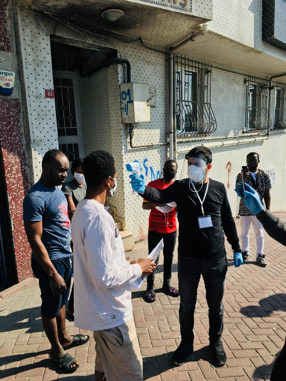Muhammed Siddik Yasar from Tarlabasi Solidarity Group using a handheld infrared thermometer gun to measure the temperature of a member of the Sierra Leone community.